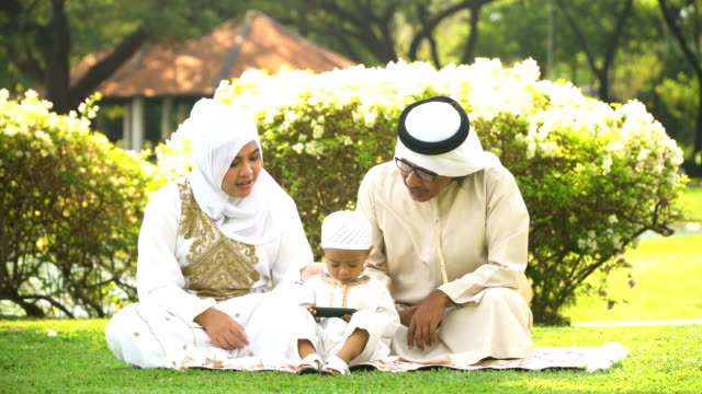 vidéos et rushes de famille musulmane ayant pique-nique avec smartphone en parc public en matinée - son