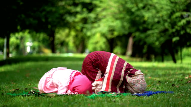 muslim family prayer for god. muslim mother and kid on their knees praying god - praying stock videos & royalty-free footage