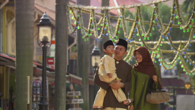 MS, CU, FOCUSING, Muslim family with son (2-3) walking on street, Singapore