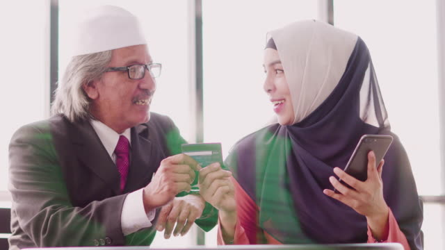 muslim father and daughter shopping online with credit card and smartphone. - kufi stock videos & royalty-free footage