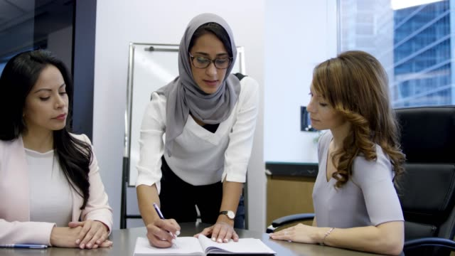 vídeos y material grabado en eventos de stock de mujer musulmana líder de negocios trabajando con su equipo - secretaria
