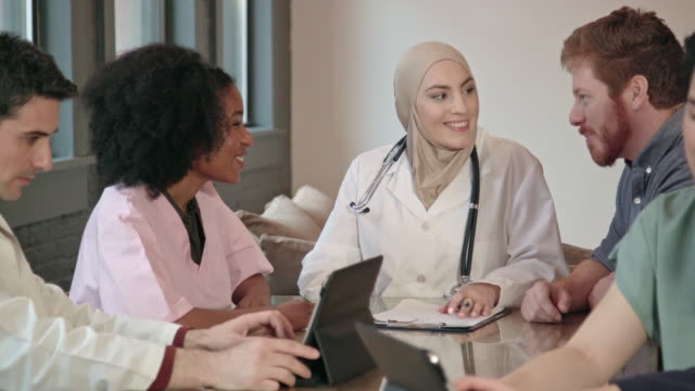 muslim female doctor leads multi-ethnic medical team mcu - hijab stock videos & royalty-free footage