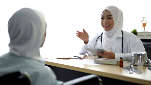 muslim female doctor talking with muslim patient in a doctor's office - islam stock videos & royalty-free footage