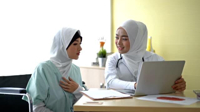 4k muslimische weibliche ärztin mit einem laptop-computer diskutieren mit patient in arztpraxis - indischer abstammung stock-videos und b-roll-filmmaterial