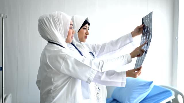 4k muslim female doctors analyzing mri scans - medical occupation stock videos & royalty-free footage