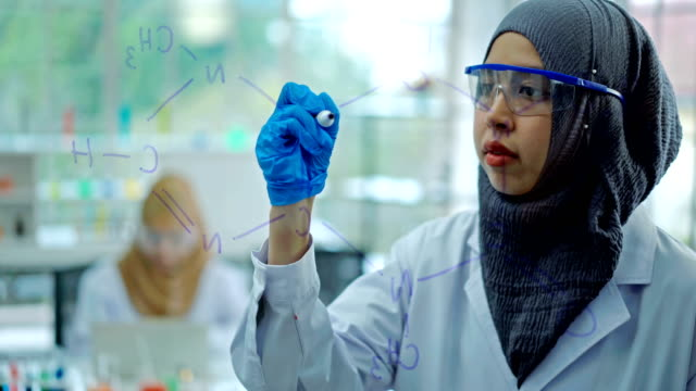 4k muslim female scientist drawing formula chemical on transparent board in laboratory - religion stock videos & royalty-free footage