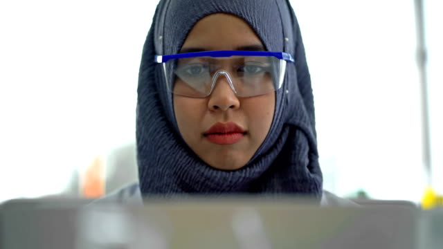 4k muslim female scientist using a laptop computer working research in laboratory - hijab stock videos & royalty-free footage