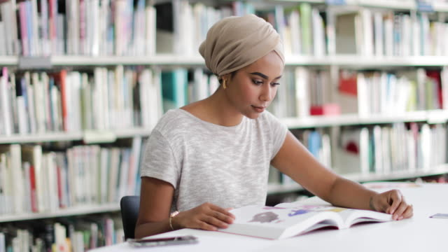 muslim female student in college library - university stock videos & royalty-free footage