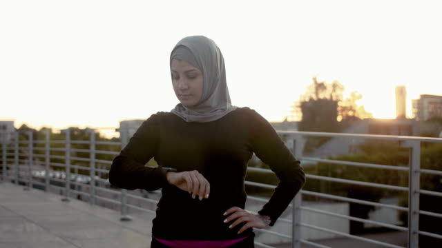 muslim fitness woman in hijab checking smart watch (slow motion) - hijab stock videos and b-roll footage