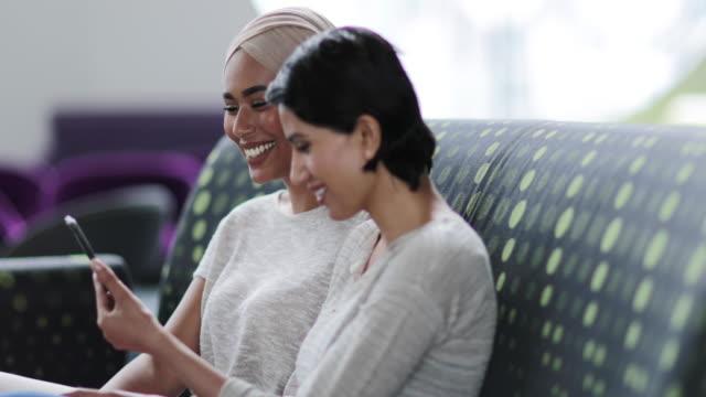 Muslim friends looking at smartphone