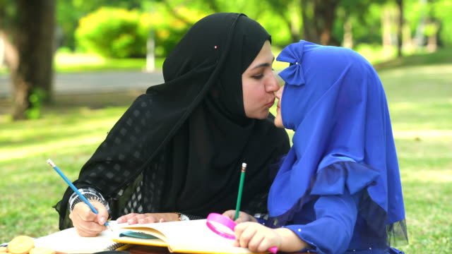 vídeos de stock e filmes b-roll de muslim girl kiss with her mother while having picnic in public park in morning - família com um filho
