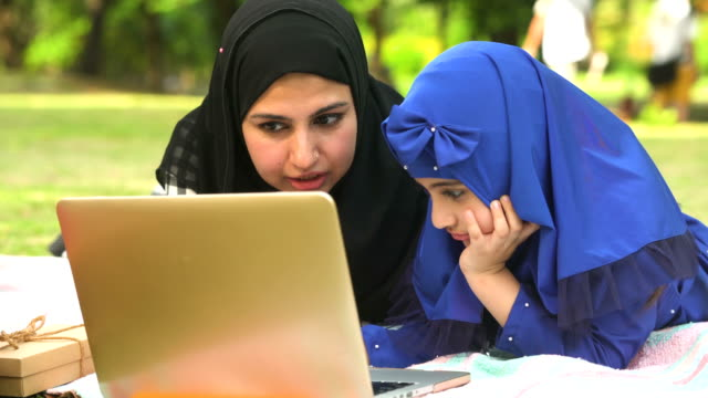 Muslim girl using notebook with her mother while having picnic in public park in morning