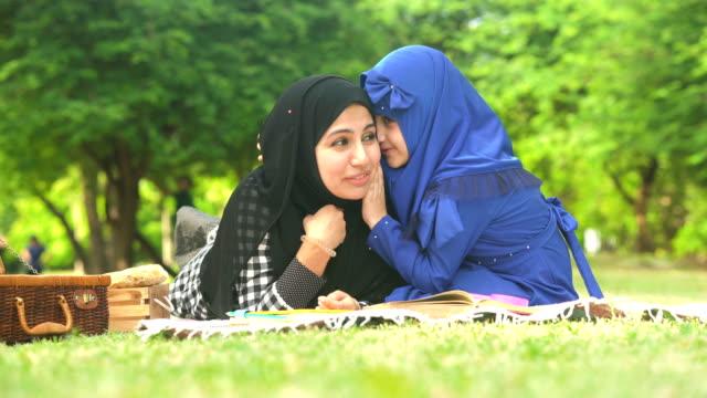vídeos de stock, filmes e b-roll de a menina muçulmana sussurra sua matriz ao ter o piquenique no parque público na manhã - whispering