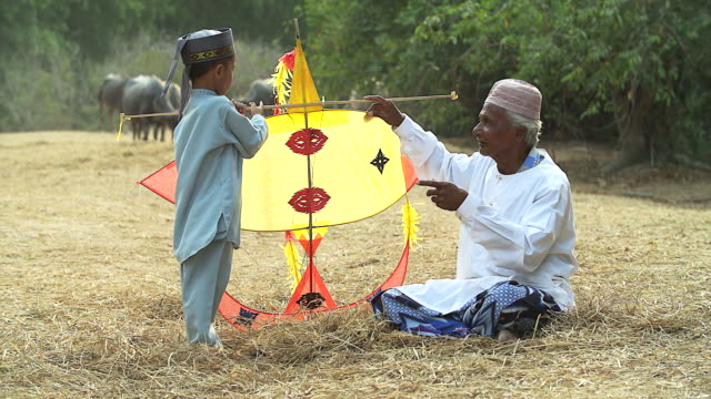 Muslim grandfather and grandson flying a kite.