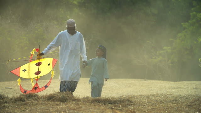 Muslim grandfather and grandson walking with a kite.