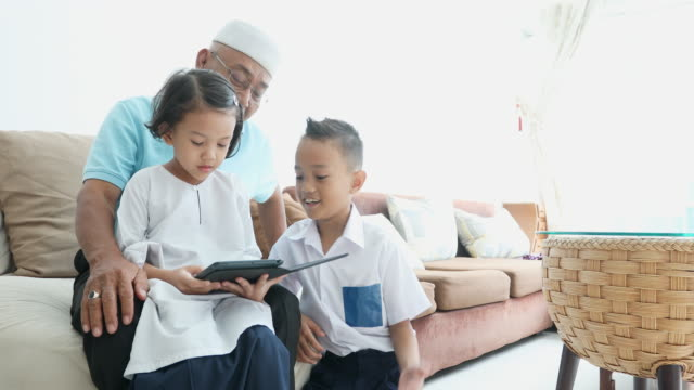 muslim grandfather reading with his grand children from a computer tablet - malay family stock videos and b-roll footage