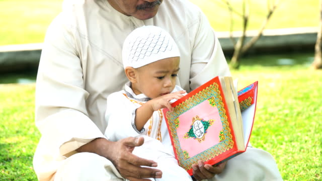 muslim grandfather teaching son reading quran public park in morning under sunlight - islam stock videos & royalty-free footage