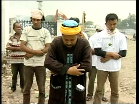 muslim holy man performing burial rites on body wrapped in yellow sheet in street as relatives stand behind him boats and wood piled up in harbour... - indonesia map stock videos & royalty-free footage