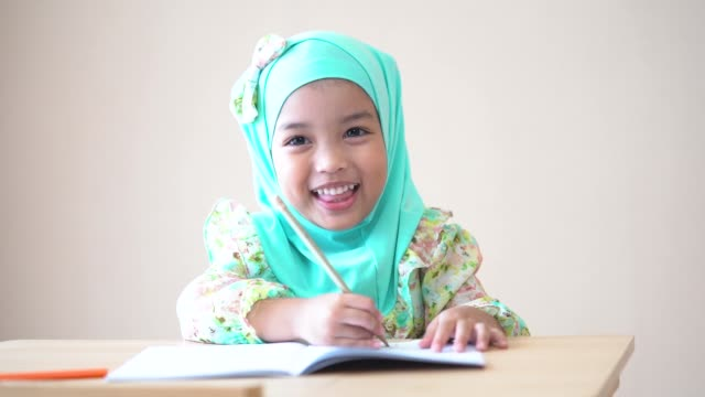 vídeos de stock e filmes b-roll de muslim kid doing homework and reading a book. kid enjoy learning with happiness at home. clever,education and smart learning concept. - soletrar