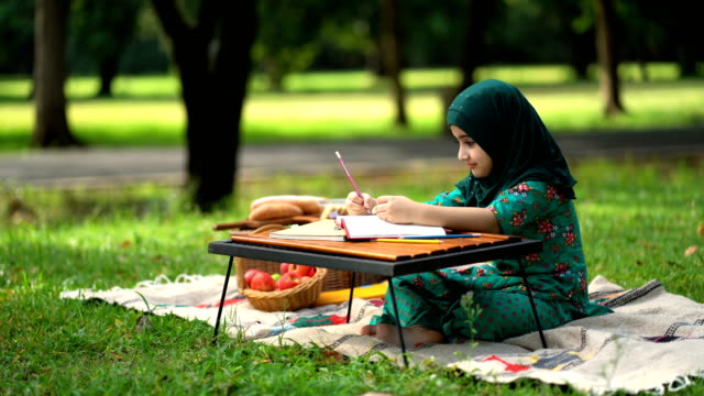 4k muslim kid reading a book in the park - saudi arabia stock videos & royalty-free footage