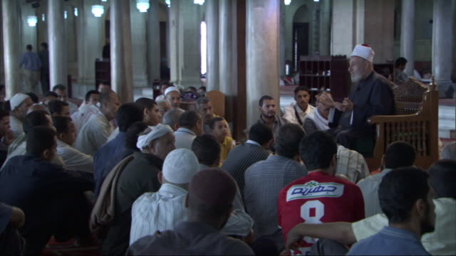 a muslim leader sits in front of and speaks to a group of men gathered in a mosque. - silence stock videos & royalty-free footage