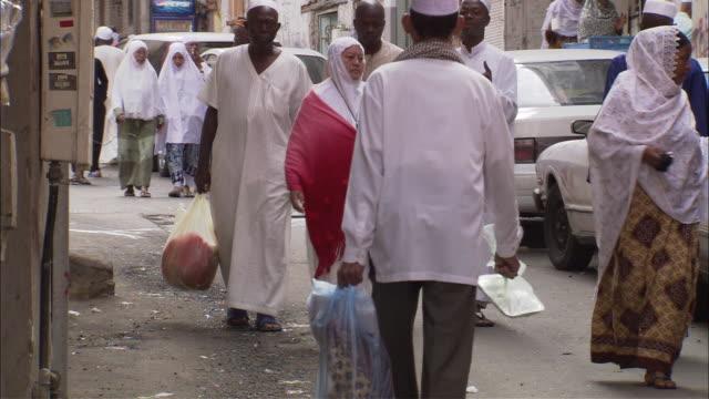 a muslim man and woman walk through a crowded street market in mecca, saudi arabia. - saudi arabia stock videos & royalty-free footage
