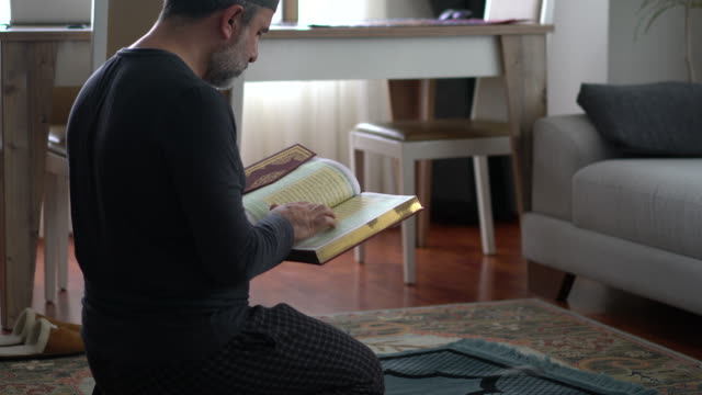 muslim man is reading the koran at home - koran stock videos & royalty-free footage