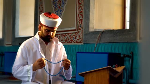 muslim man prays with a rosary - pilgrim hat stock videos & royalty-free footage
