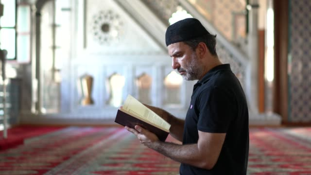 muslim man reading koran in mosque - islam stock videos & royalty-free footage