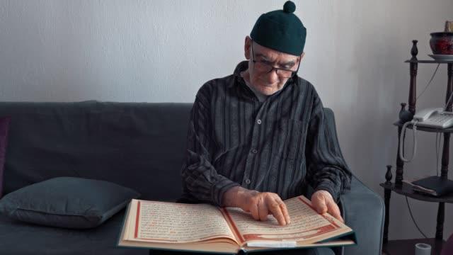 muslim man reading quran and praying at home in ramadan, - koran stock videos & royalty-free footage