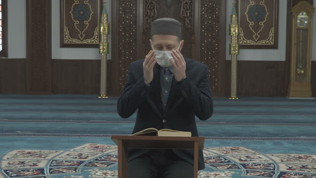 a muslim man with the mask is reading quran at mosque - ramadan stock videos & royalty-free footage