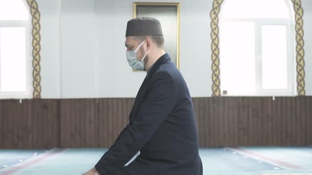 一個戴著面具祈禱清真寺的穆斯林男子 - 僅一成熟男士 個影片檔及 b 捲影像