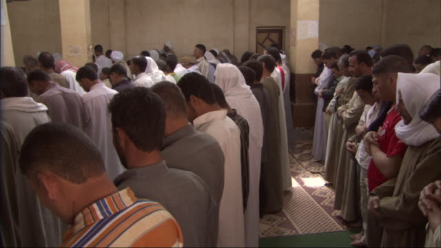 muslim men bow their heads as they stand in a church. - congregation stock videos & royalty-free footage