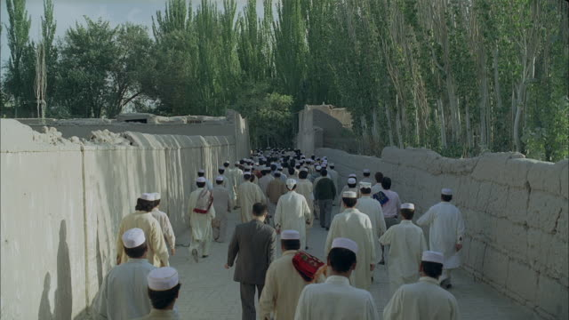 muslim men in white robes and skullcaps file through a stone corridor at a mosque in afghanistan. - 2007 stock videos & royalty-free footage
