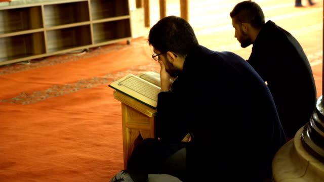 muslim men pray and read the quran together in mosque - koran stock videos & royalty-free footage