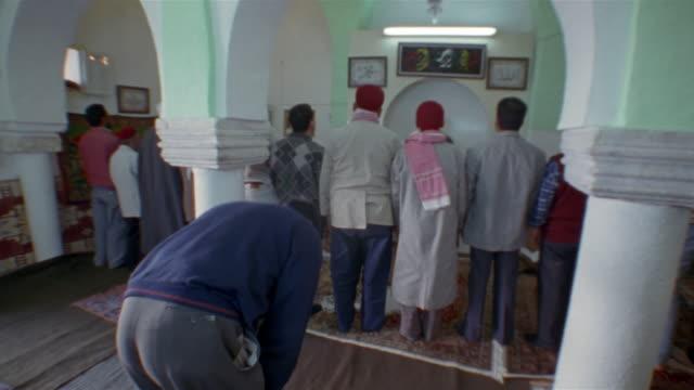 ms, muslim men praying, rear view, small mosque, kairouan, tunisia - kufi stock videos & royalty-free footage