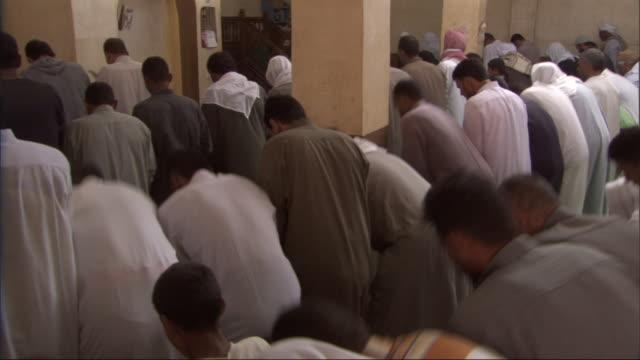 vidéos et rushes de muslim men stand in a church and then genuflect in unity. - assemblée de fidèles