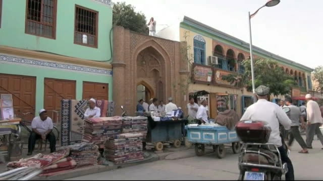 muslim minority group uighurs escape route from china: longer version; china: xinjiang province: ext city skyline statue of mao zedong people and... - 新疆ウイグル自治区点の映像素材/bロール