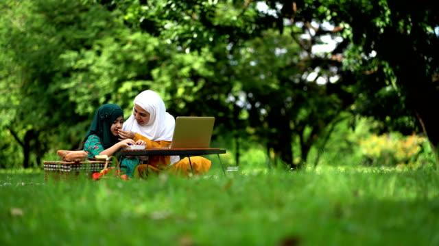 vidéos et rushes de mère et descendant musulmans ayant un pique-nique au stationnement - partage