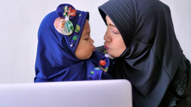muslim mother and daughter playing computer at home - kissing stock videos & royalty-free footage
