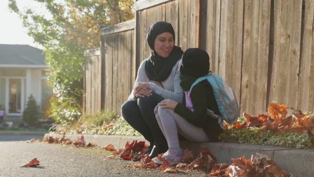 vídeos de stock, filmes e b-roll de mãe muçulmana e filha sentada no meio-fio - hijab