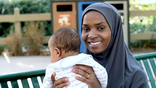 muslim mother holding her baby sitting in a park bench - islam stock videos & royalty-free footage