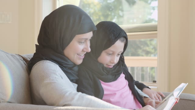 4k uhd: muslim mother reading to her daughter - emigration and immigration stock videos & royalty-free footage