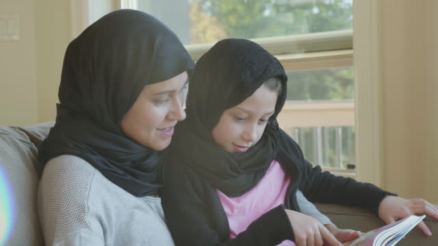 muslim mother reading with her daughter - islam stock videos & royalty-free footage