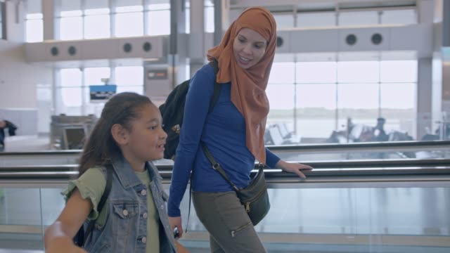 muslim mother wearing hijab and young daughter walk along moving sidewalk in airport terminal. tracking shot. - islam stock videos & royalty-free footage