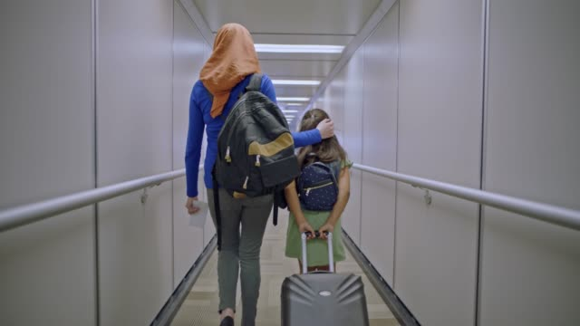 vídeos de stock e filmes b-roll de muslim mother wearing hijab places loving hand on young daughter's head as they walk down airport jet bridge. - avião comercial