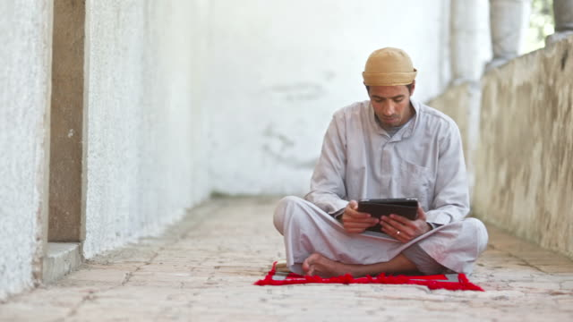 hd dolly: muslim pilgrim using digital tablet - islam stock videos & royalty-free footage