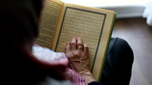 dolly shot: muslim senior woman with headscarf reading holy koran - koran stock videos & royalty-free footage