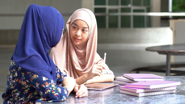 vídeos de stock e filmes b-roll de muslim university college students reading book together - indonesia