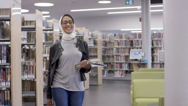 muslim university student walking through the library - islam stock videos & royalty-free footage